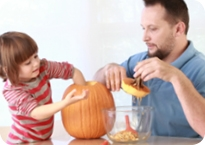 Man and a child carving a pumpkin