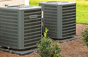 Two ac units outside of a house