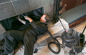 A professional chimney sweep cleaning a chimney