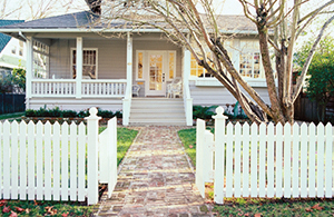 front of a home with white picket fence