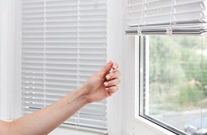 Woman adjusting blinds on a window