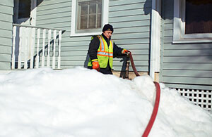 Petro delivery driver surrounded by snow with a hose attached to the home's cleared fill pipe